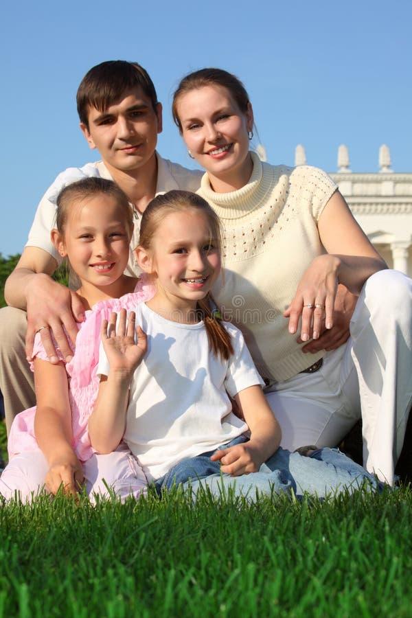 La famille de quatre extérieurs en été se repose sur l'herbe images stock