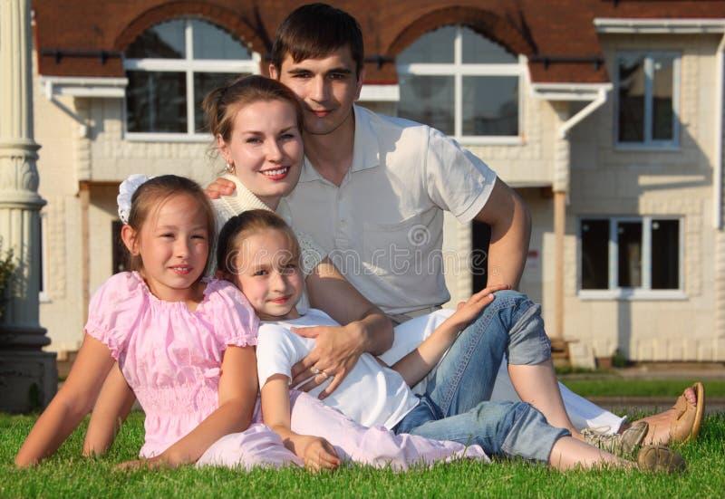 La famille de quatre s'assied sur l'herbe contre la maison image libre de droits