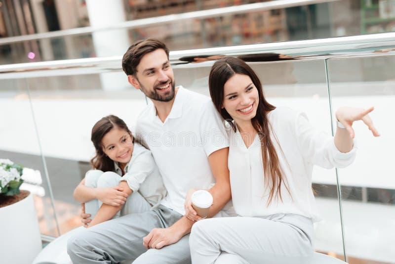 La famille de trois, le père, la mère et la fille s'asseyent sur le banc dans le centre commercial image libre de droits