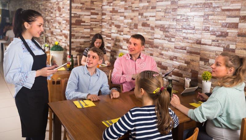 La famille donnent l'ordre à la serveuse gaie images libres de droits