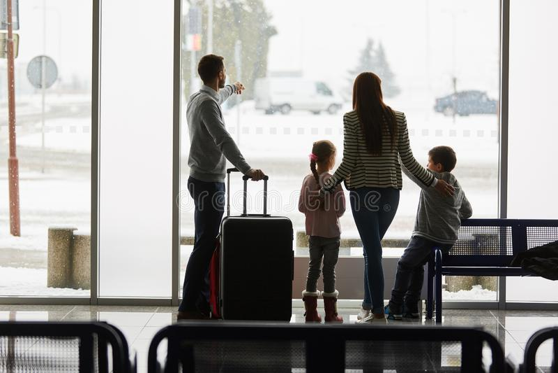 La famille et les enfants attendent le vol de correspondance dans l'aéroport images libres de droits