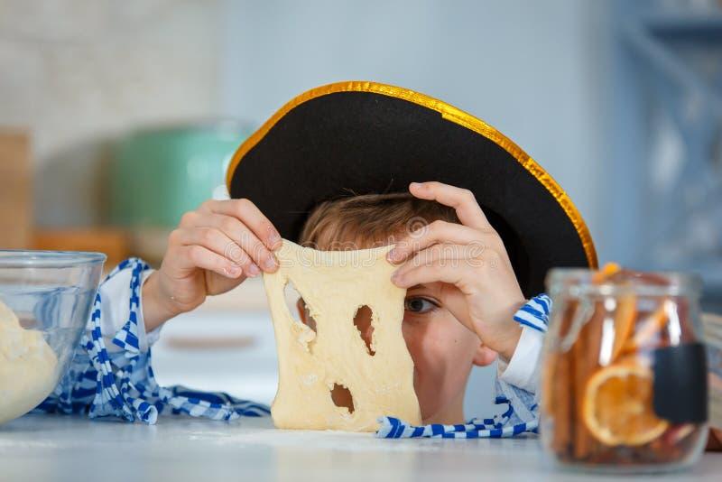 La famille fait cuire ensemble Le fils malaxe la pâte avec de la farine image libre de droits