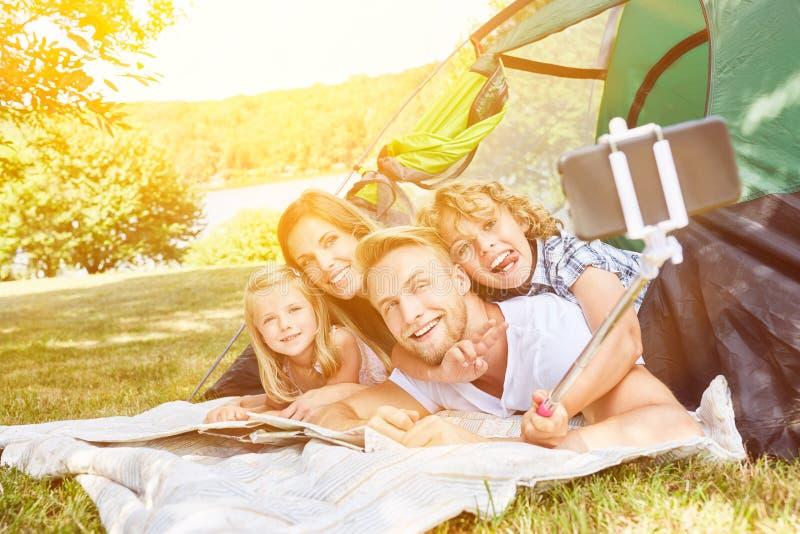 La famille fait le selfie avec le bâton de selfie tout en campant photographie stock libre de droits