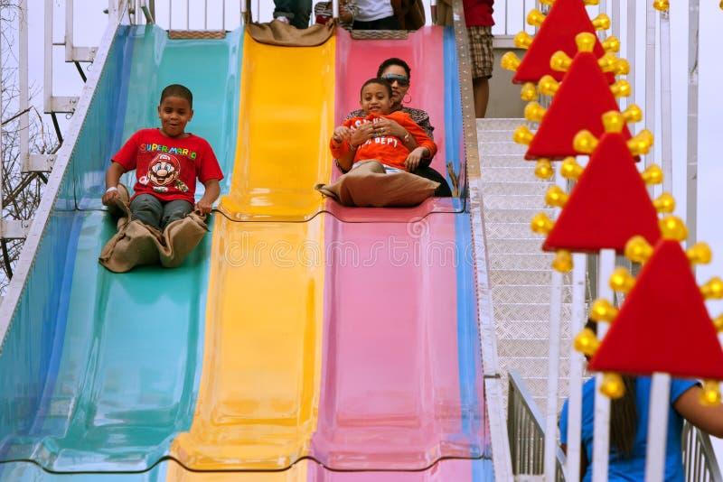 La famille glisse vers le bas la glissière d'amusement à Atlanta loyalement images libres de droits