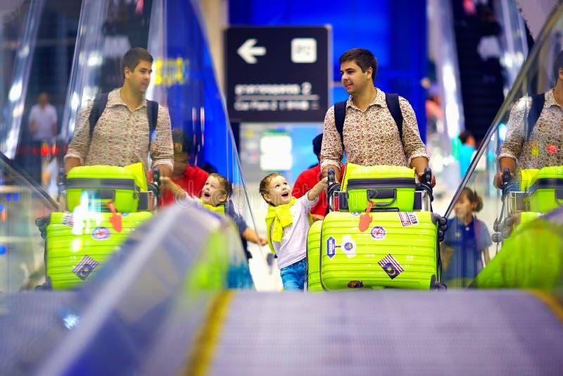 La famille heureuse avec des bagages sur le convoyeur dans l'aéroport, préparent pour voyager photographie stock libre de droits