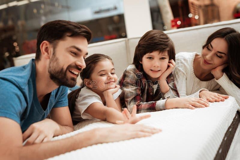 La famille heureuse détend sur le matelas dans le magasin de meubles orthopédique Grande douceur de contrôle de famille de matela photos libres de droits