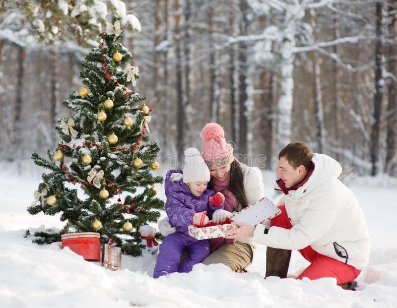 La famille heureuse donne des cadeaux dans la forêt d'hiver photos stock
