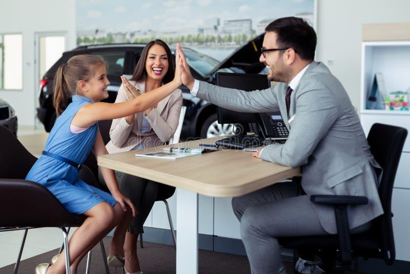 La famille heureuse et enthousiaste célébrant juste a acheté une nouvelle voiture de concessionnaire images libres de droits