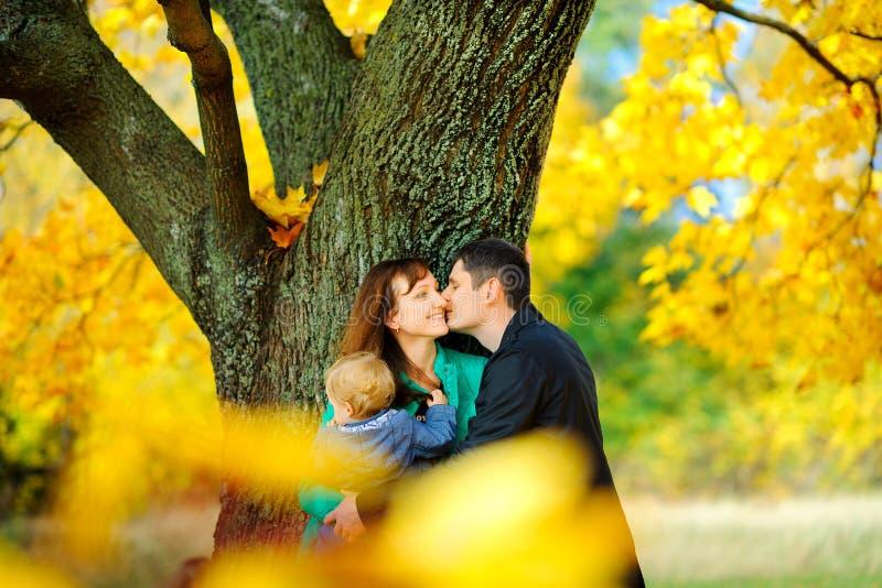La famille heureuse flâne en parc d'automne image libre de droits