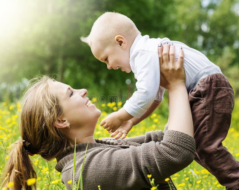 La famille heureuse, mère soulève son fils sur le fond de nature photos stock