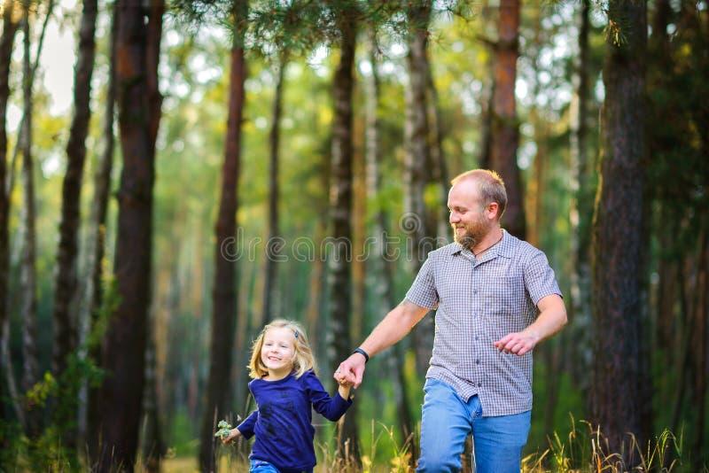 La famille heureuse marche en parc égalisant, tenant des mains images stock