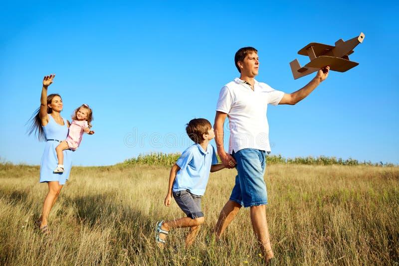 La famille heureuse marche sur la nature en été image stock