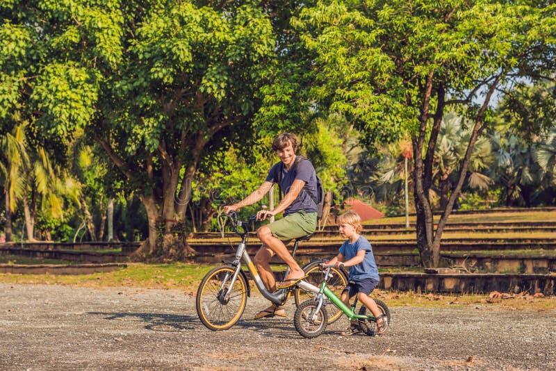 La famille heureuse monte des vélos dehors et le sourire Engendrez sur un vélo et un fils sur un balancebike photo stock