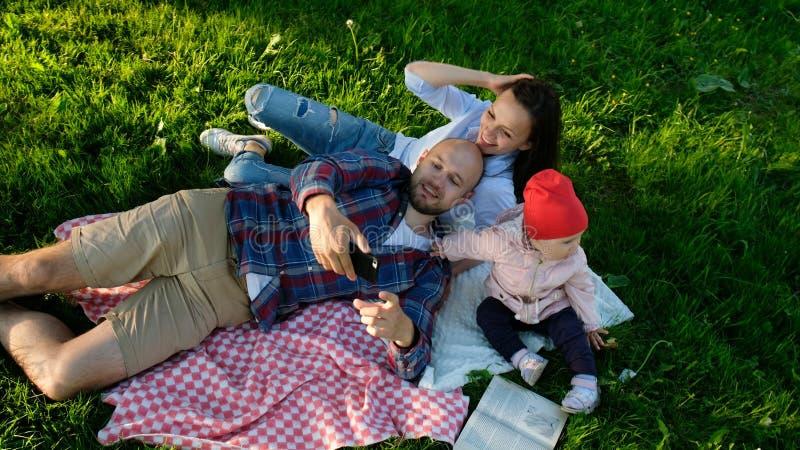 La famille heureuse s'étend sur le selfie parlé en faveur et faisant avec un bébé au coucher du soleil en parc Le père et la mère image stock