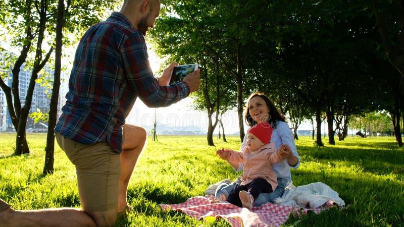 La famille heureuse s'étend sur le selfie parlé en faveur et faisant avec un bébé au coucher du soleil en parc Le père prend des  photos libres de droits