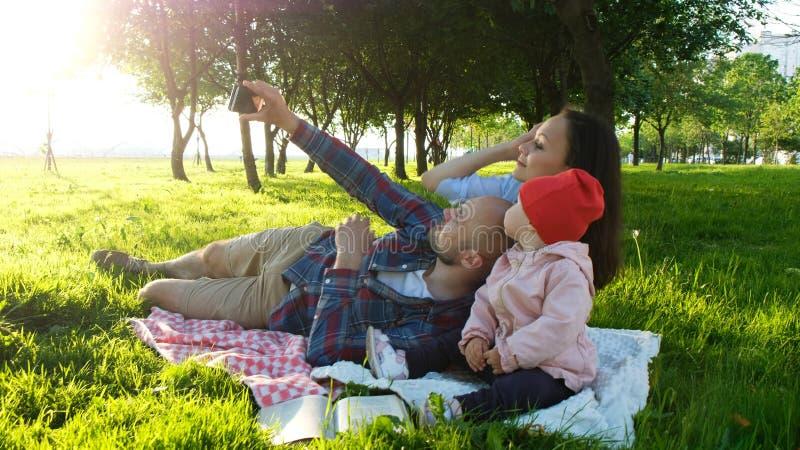 La famille heureuse s'étend sur le selfie parlé en faveur et faisant avec un bébé au coucher du soleil en parc Le père prend des  photo stock