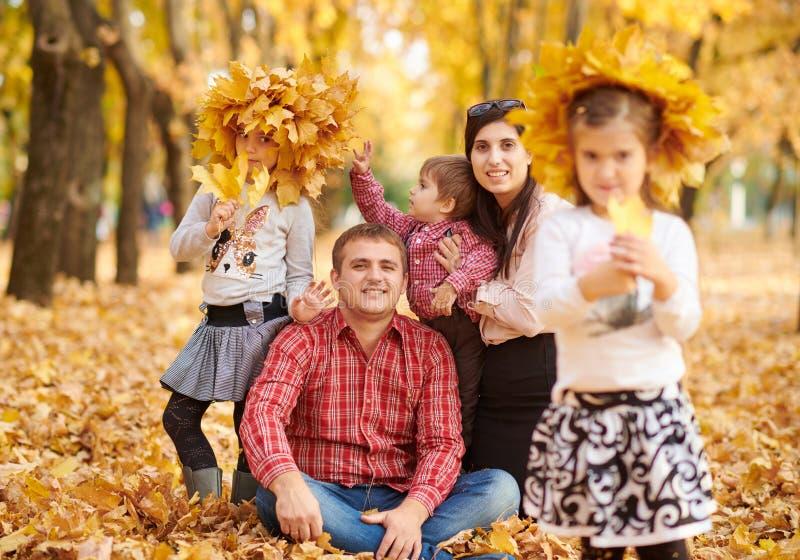 La famille heureuse s'assied en parc de ville d'automne Enfants et parents Ils posant, souriant, jouant et ayant l'amusement Jaun photographie stock libre de droits