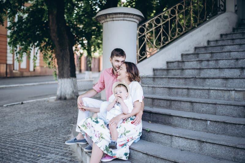 La famille heureuse s'assied sur les escaliers avec un petit garçon blond sur ses genoux du ` s de mère Image avec le foyer sélec photographie stock