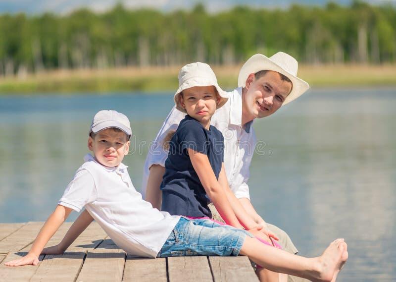 La famille heureuse se repose sur un pilier en bois photographie stock libre de droits