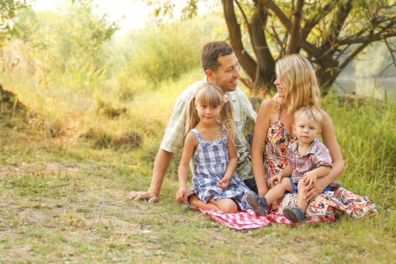 La famille heureuse sur la nature des enfants se repose avec le fond de route photo stock