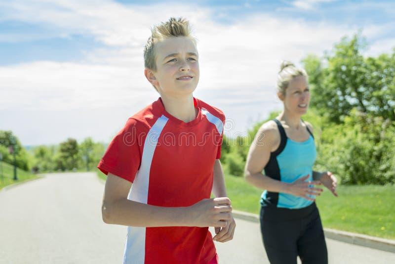 La famille, la mère et le fils sont courants ou pulsants pour le sport dehors photo stock