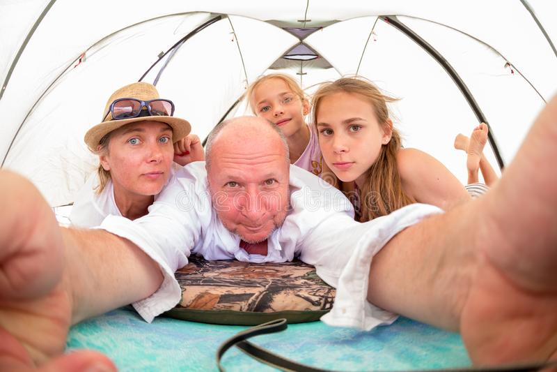 La famille, la maman, le papa et deux enfants prennent des photos d'elles-mêmes des vacances photo stock
