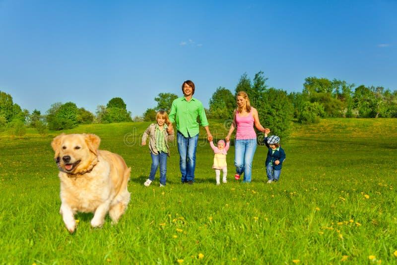 La famille marche avec le chien courant en parc image libre de droits