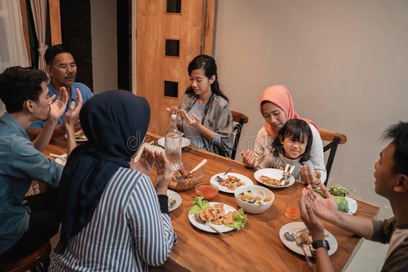 La famille musulmane prient avant d?ner photos stock