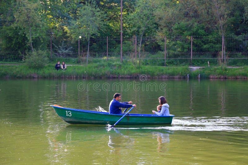 La famille naviguent dans le bateau à rames vert images libres de droits