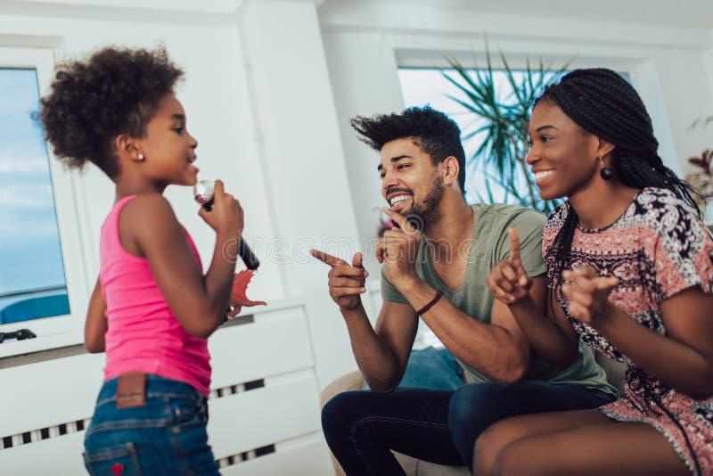 La famille noire ont plaisir à chanter le karaoke photographie stock