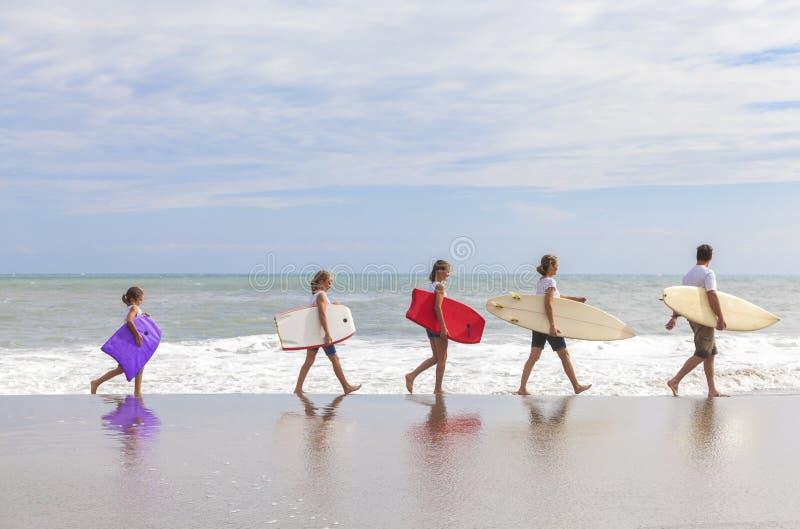 La famille Parents des planches de surf d'enfants de fille sur la plage image libre de droits