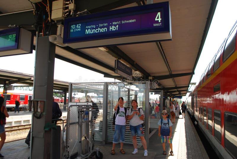 La famille regarde l'affichage indiquant la destination du train images libres de droits