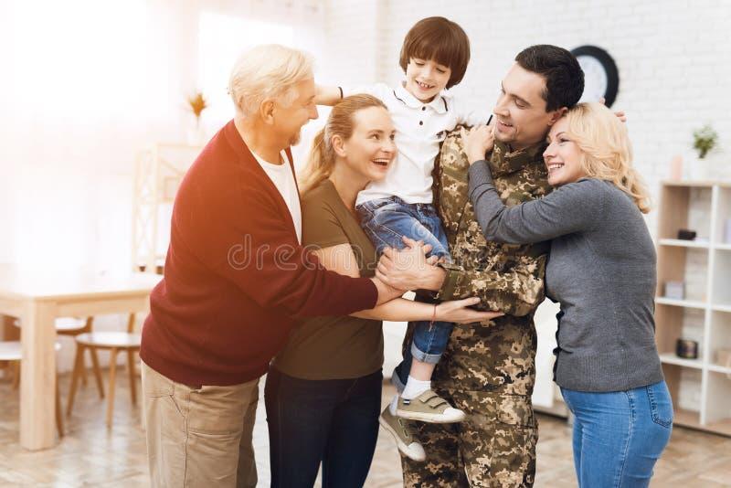 La famille rencontre un homme dans le camouflage à la maison photo libre de droits