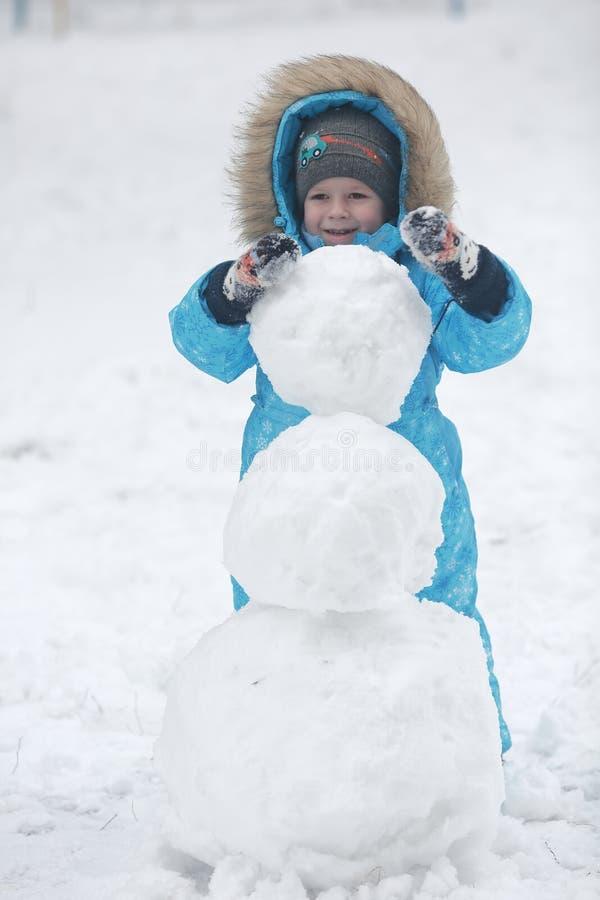 La famille sculpte le bonhomme de neige photos stock