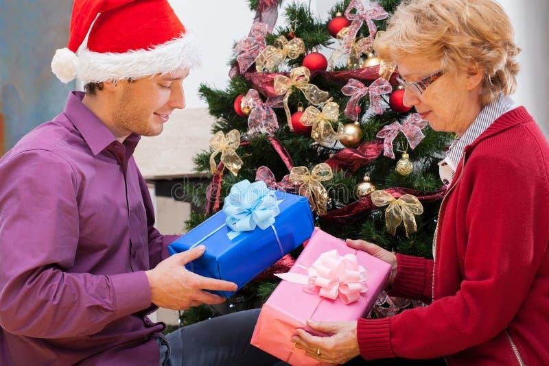 La famille se donnant a enveloppé des cadeaux de Noël image stock