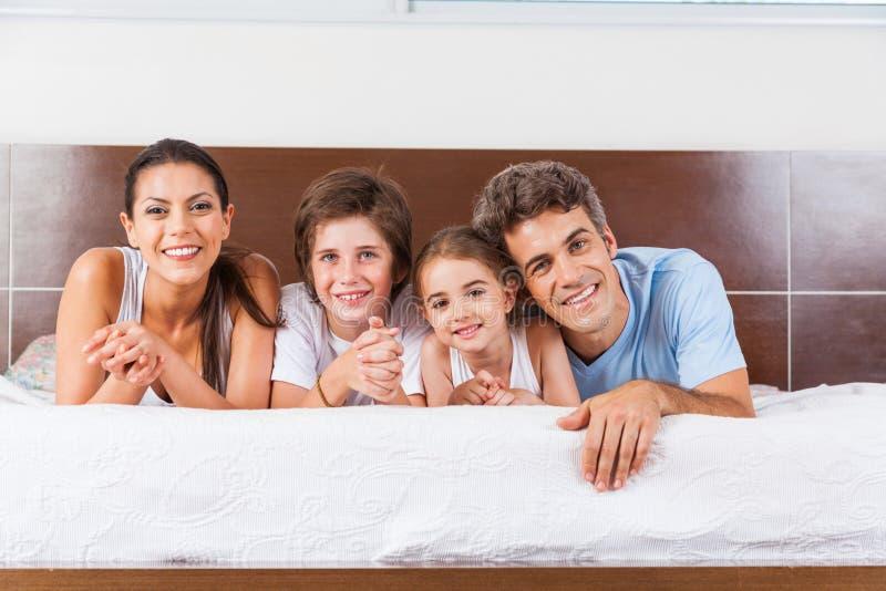 La famille se trouvant sur un couple de lit parents avec des enfants image libre de droits