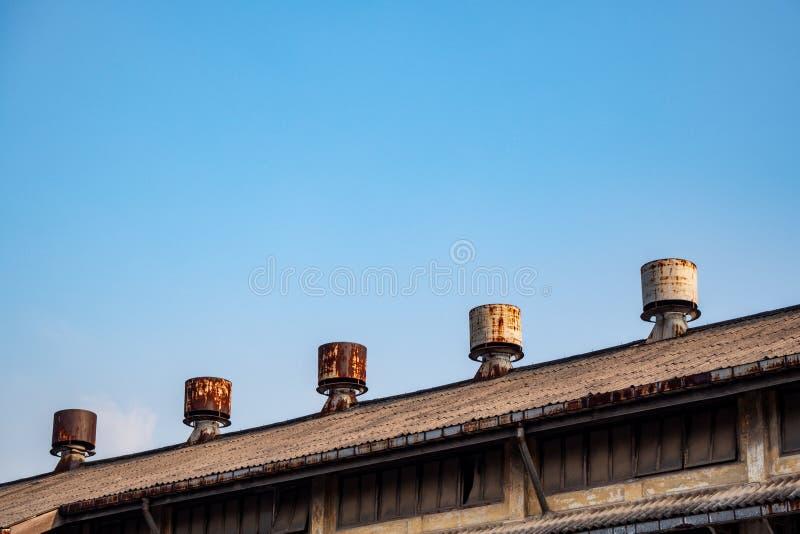 La fan del respiradero está en el tejado de la fábrica vieja con el fondo del cielo azul fotos de archivo