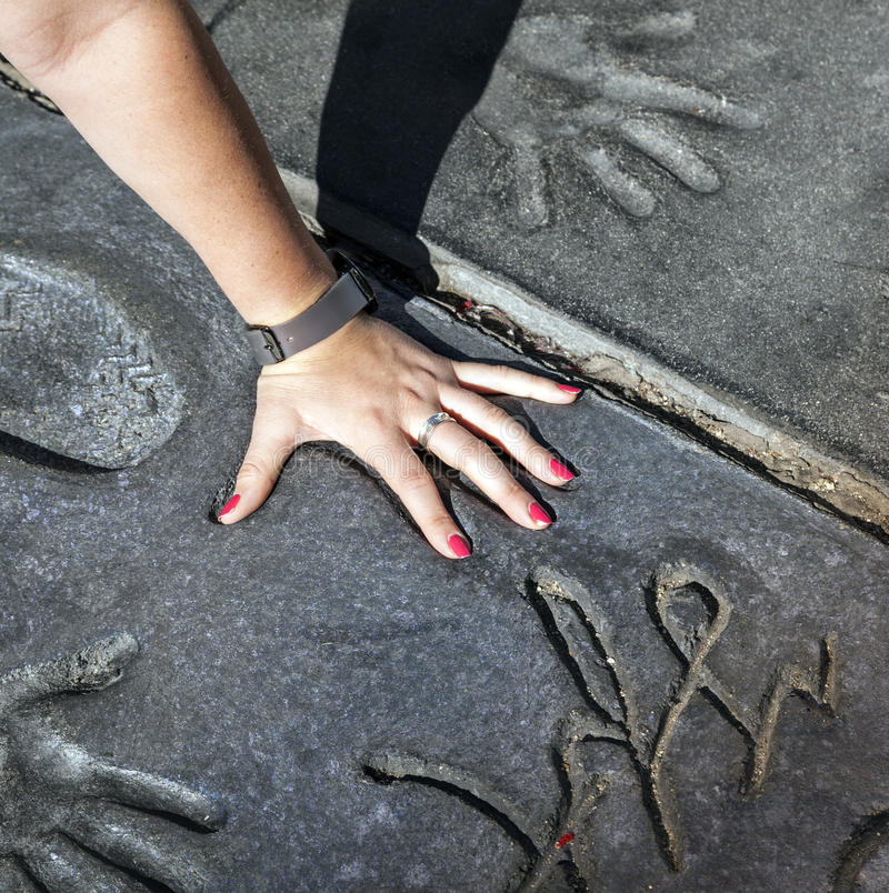 La fan pone la mano en los handprints de las estrellas crepusculares de la saga imagen de archivo