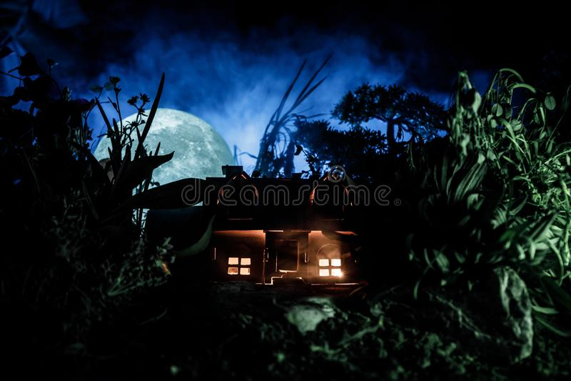 La fantasía adornó la foto Pequeña casa hermosa en hierba con la luz Casa vieja en bosque en la noche con la luna Foco selectivo imágenes de archivo libres de regalías