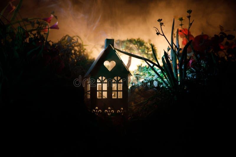 La fantasia ha decorato la foto Piccola bella casa in erba con luce Vecchia casa in foresta alla notte con la luna Fuoco selettiv immagini stock libere da diritti