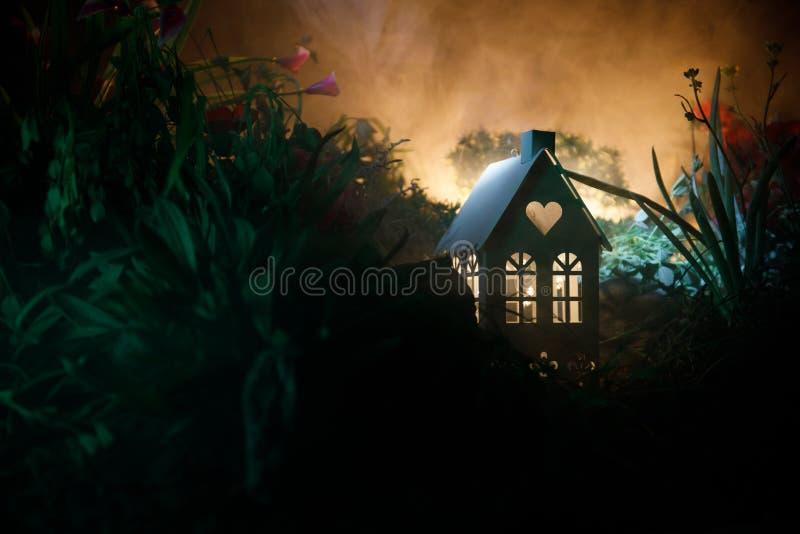 La fantasia ha decorato la foto Piccola bella casa in erba con luce Vecchia casa in foresta alla notte con la luna Fuoco selettiv immagini stock