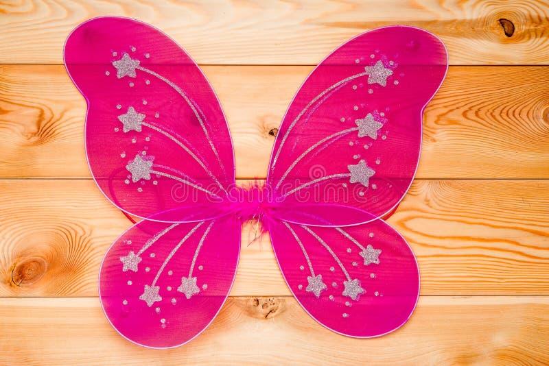La farfalla rosa traversa il costume volando per un carnevale per una ragazza su di legno immagine stock libera da diritti