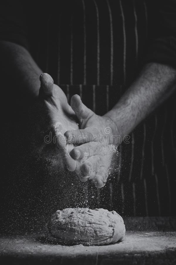 La farina è spruzzata a mano sopra una palla di pasta su un bordo di legno nella conversione artistica immagini stock