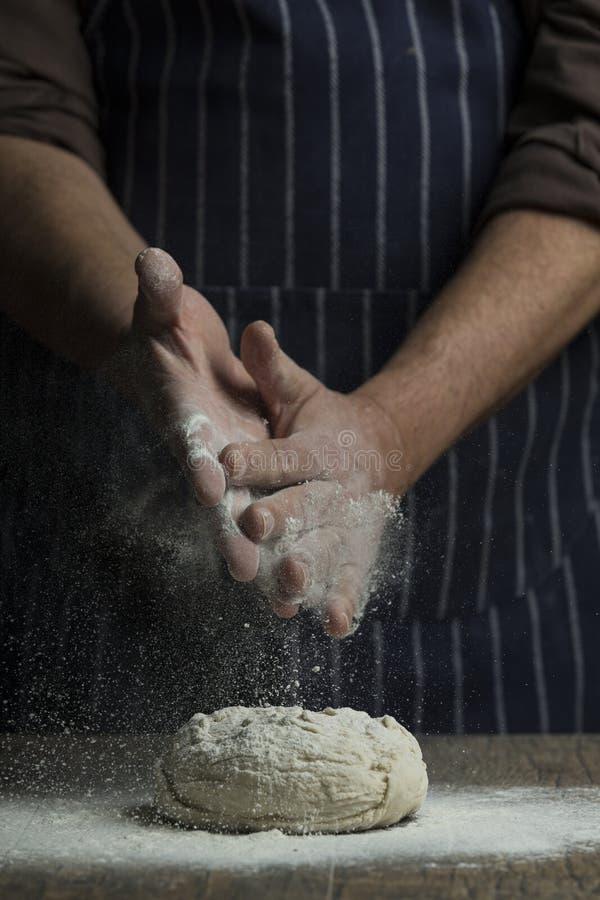 La farina è spruzzata a mano sopra una palla di pasta sul bordo di legno fotografia stock libera da diritti