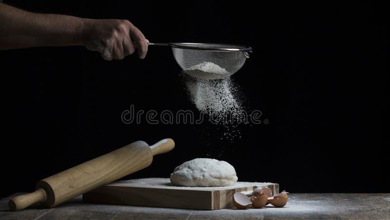 La farina è spruzzata sopra una palla di pasta su un bordo di legno con il rullo immagini stock