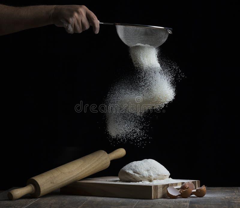 La farina è spruzzata sopra una palla di pasta su un bordo di legno con la r immagini stock libere da diritti
