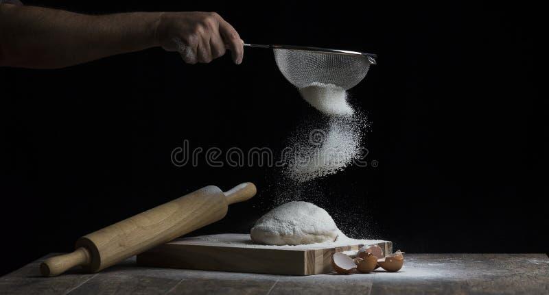 La farina è spruzzata sopra una palla di pasta su un bordo di legno con la r fotografia stock libera da diritti