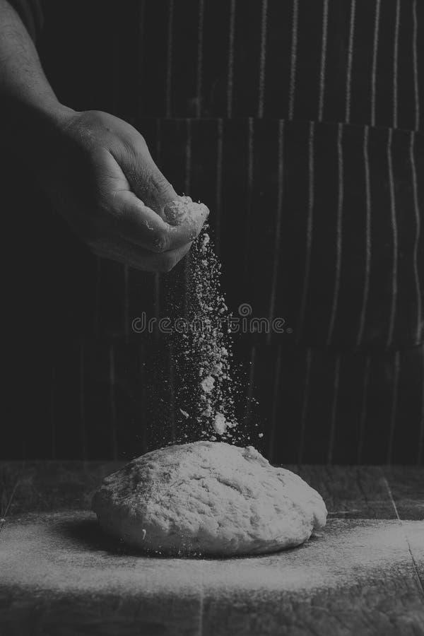 La farina è spruzzata sopra una palla di pasta su un bordo di legno da Han fotografia stock libera da diritti