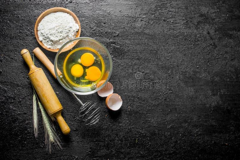 La farina con le uova, sbatte e matterello fotografia stock