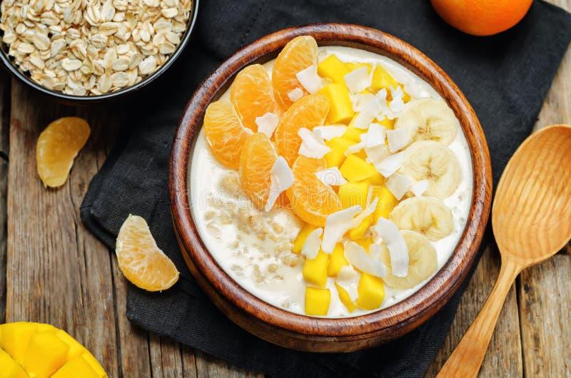 La farina d'avena con il mango, la banana, le arance del mandarino e la noce di cocco si sfalda fotografia stock